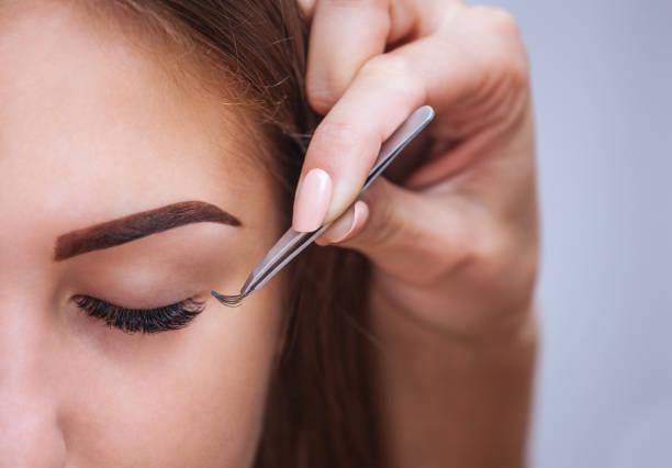 make-up-meister korrigiert und stärkt die wimpern balken, hält sich der pinzette in einem schönheitssalon. - haarverlängerung stock-fotos und bilder