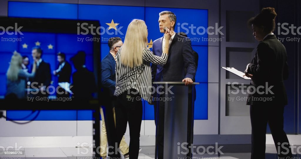 Makeup men preparing politician for announcement stock photo