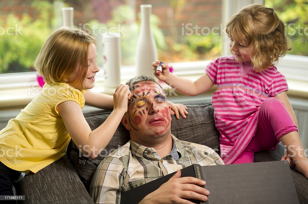 make-up mischief dad falls asleep and the children get out the make up box** book spine has the word 'classic' which is not the logo or company name ** 40-44 Years Stock Photo