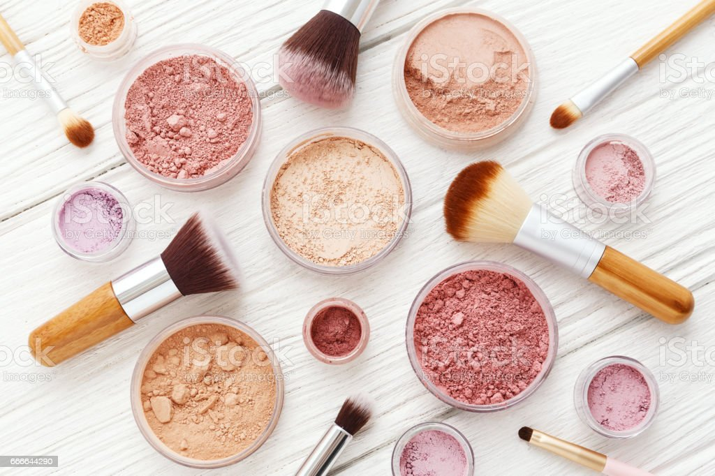 Makeup powder and brushes on white wood flat lay stock photo
