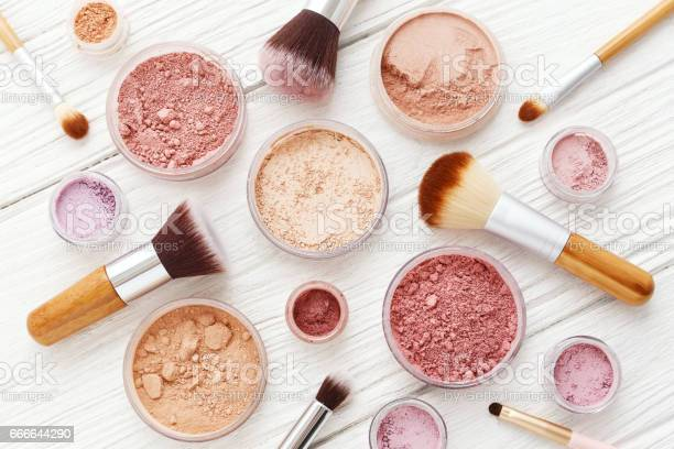 Makeup powder products with foundation blush eye shadow and brush on white wood background flat lay