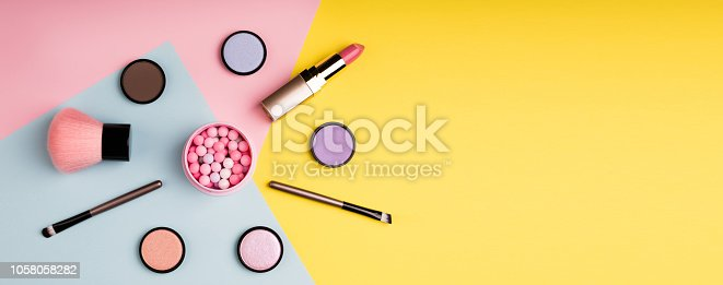 istock Makeup products and decorative cosmetics on color background flat lay. Fashion and beauty blogging concept. Long web format 1058058282
