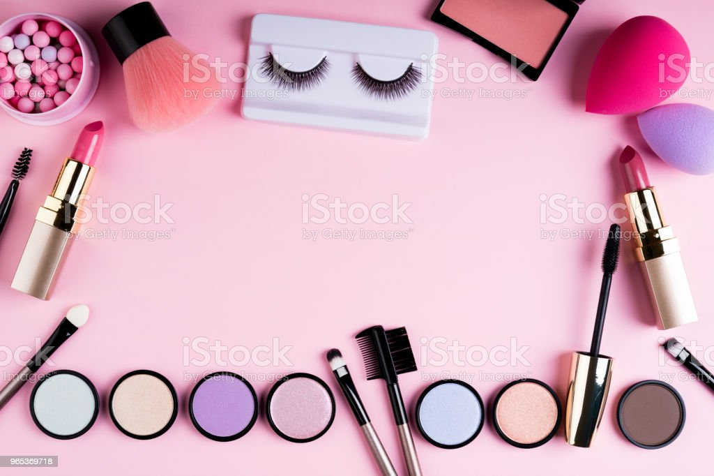Makeup products and decorative cosmetics on pink background flat lay. Fashion and beauty blogging concept