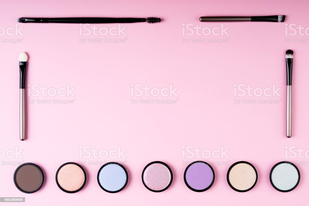 Makeup products eyeshadow and cosmetics accessories on pink background flat lay. Fashion and beauty blogging