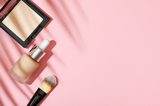 Makeup products for skin tone. Brush for foundation, bb cream, powder in a square case on a pink background top view with the shadow of a palm leaf. Cosmetics for professional makeup artist flat lay.