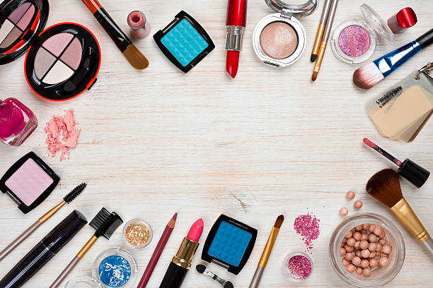 Makeup products on wooden background with copy space in center stock photo