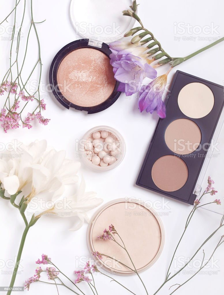 Makeup products surrounded by pink and white flowers on white...
