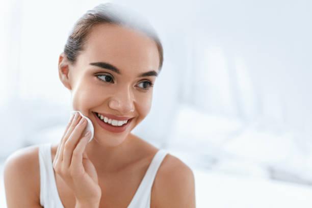 suppression de maquillage. fille nettoyant visage peau avec cosmétique - démaquillant photos et images de collection