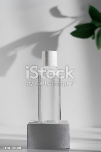 istock Makeup remover, natural moisturizing lotion mockup close up. Transparent liquid container side view. Organic cosmetics poster concept. Micellar water bottle and blurred leaves on background 1173191095