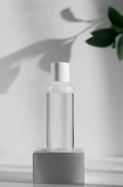 Makeup remover, natural moisturizing lotion mockup close up. Transparent liquid container side view. Organic cosmetics poster concept. Micellar water bottle and blurred leaves on background stock photo
