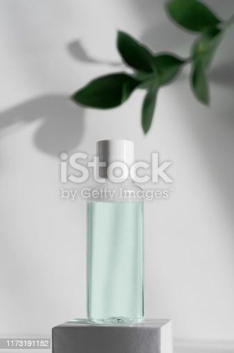 istock Makeup remover, natural moisturizing lotion mockup close up. Transparent liquid container side view. Organic cosmetics poster concept. Micellar water bottle and blurred leaves on background 1173191152
