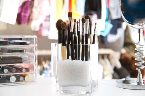 Beauty organizer of brushes for make up and mirror, with cloths hanging at background. The place is a walk-in closet full of color.