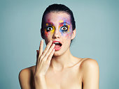 Studio shot of an attractive young woman with brightly colored makeup against a blue background