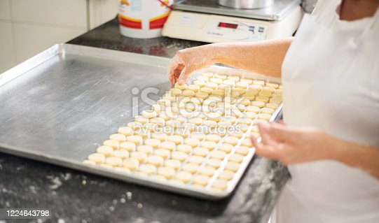 Close up of a female baker hands arranging cookies in baking tray at the bakery