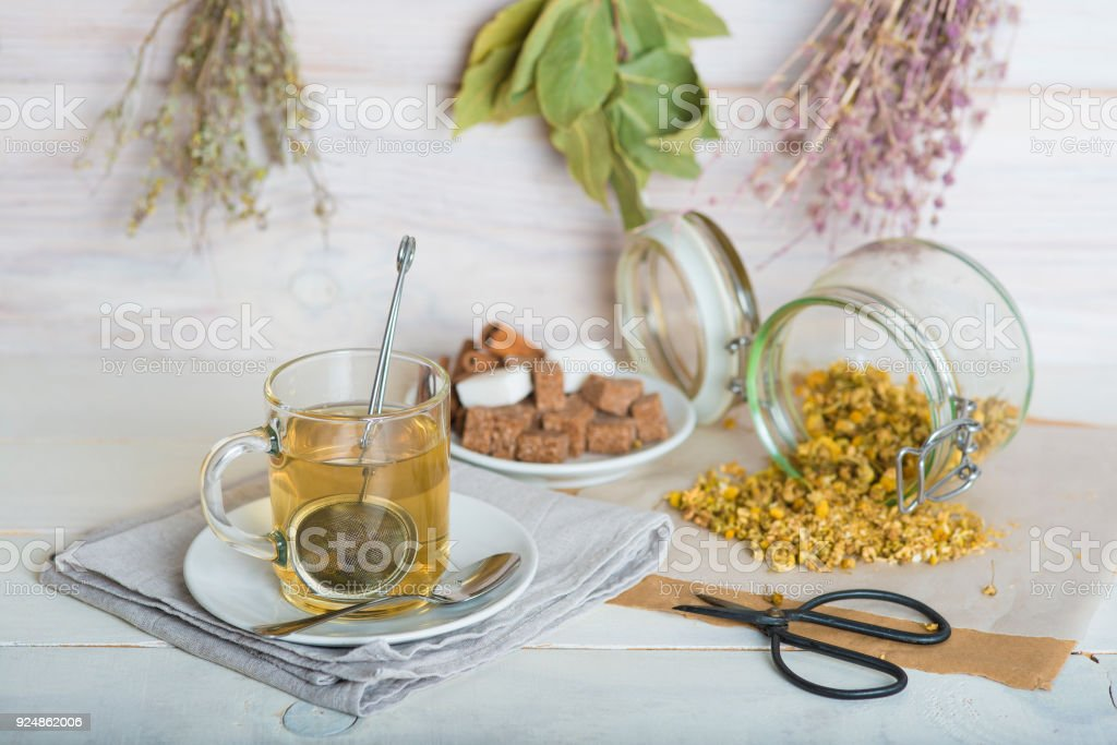 Making a beverage with chamomile flowers and a mesh ball tea infuser stock photo