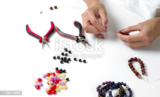 1074436306istockphoto Making a bracelet of colorful beads. Female hands with a tool on a white background 1136216882