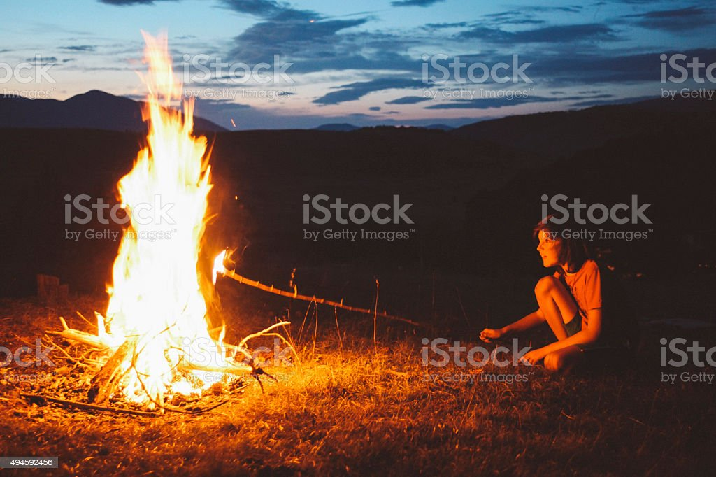 Vintage toned, low key image of a young boy, making a campfire in the...