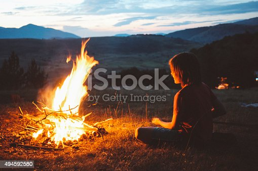 Vintage toned, low key image of a young boy, making a campfire in the nature as the sun sets down.