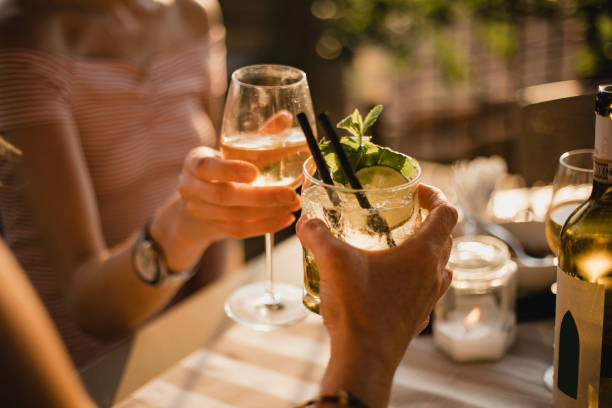 Making a Celebratory Toast Two unrecognisable people sitting down at a table during sunset, they are making a celebratory garnish stock pictures, royalty-free photos & images