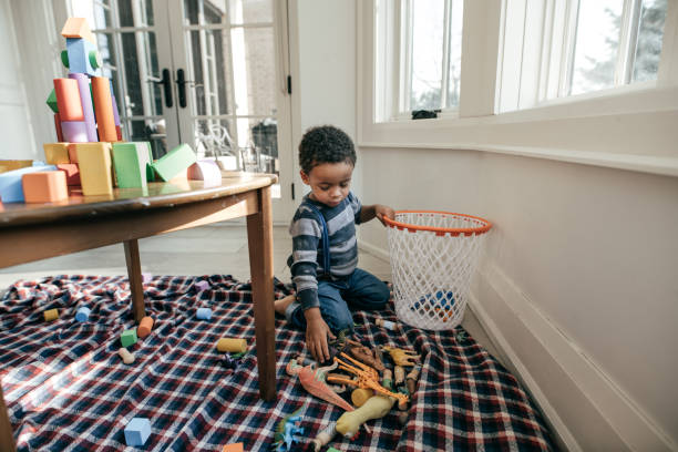 Making a child responsible. Child picking up his toys. chores stock pictures, royalty-free photos & images