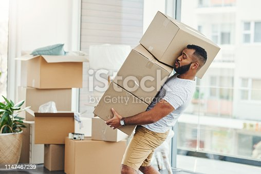 Shot of a young man carrying a pile of boxes while moving house