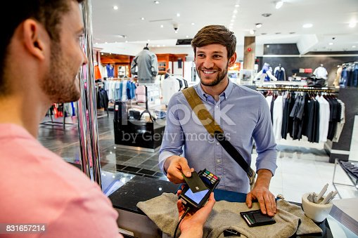 A young man in a fashionable clothing store, making a contactless payment with his bank card to buy new clothes