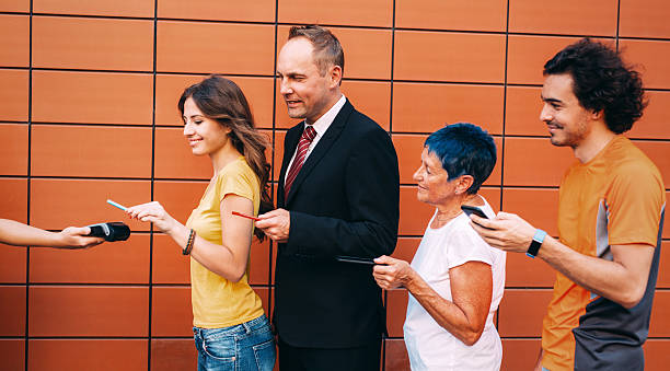 Making a contactless payment with smartphone Group of people making a contactless payment with smartphone. age contrast stock pictures, royalty-free photos & images
