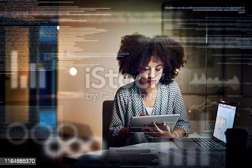 Shot of a young female programmer using a digital tablet while working late in her office