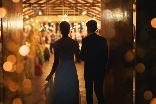 Making a grand entrance into marriage Rearview shot of a young couple arriving hand in hand at their wedding reception romance stock pictures, royalty-free photos & images