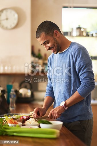Shot of a happy young man preparing a healthy snack at home