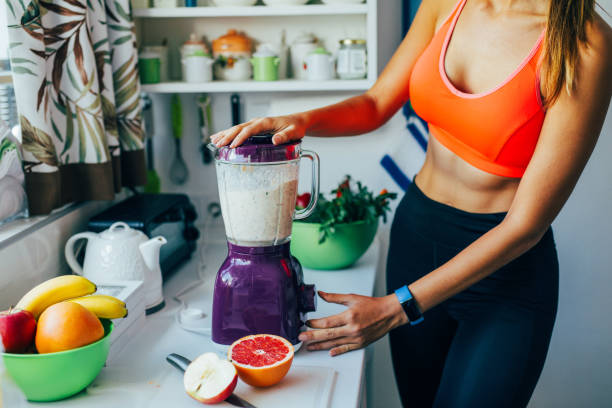 Making a healthy smoothie on a blender Sportswoman making a healthy smoothie on a blender. blender stock pictures, royalty-free photos & images