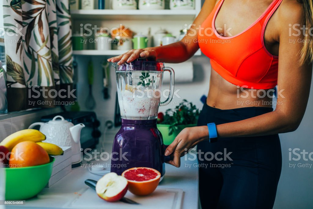 Making a healthy smoothie on a blender stock photo