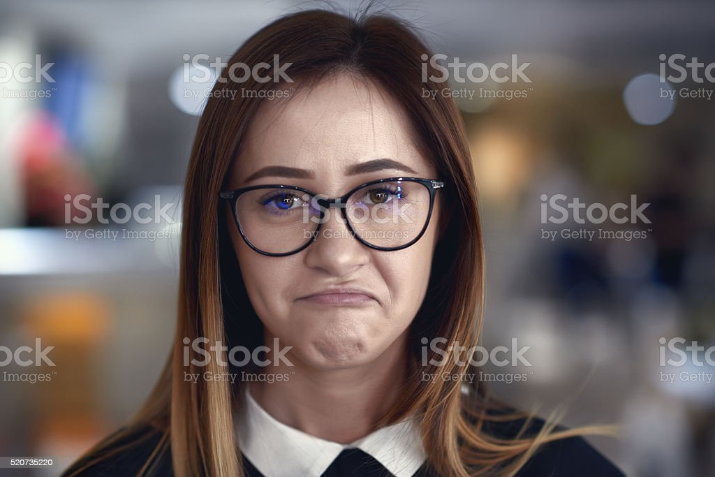 making a nerd face front view of young woman with brown hair looking at camera with confused expression.wearing nerd eyeglasses. 20-24 Years Stock Photo