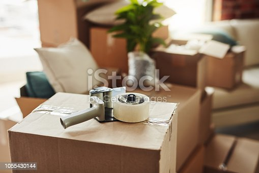 Still life shot of a tape dispenser on a cardboard box in a house