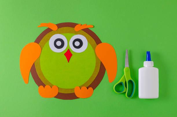 machen eine eule mit farbenpapier, klebstoff und schere auf grün - diy eule stock-fotos und bilder