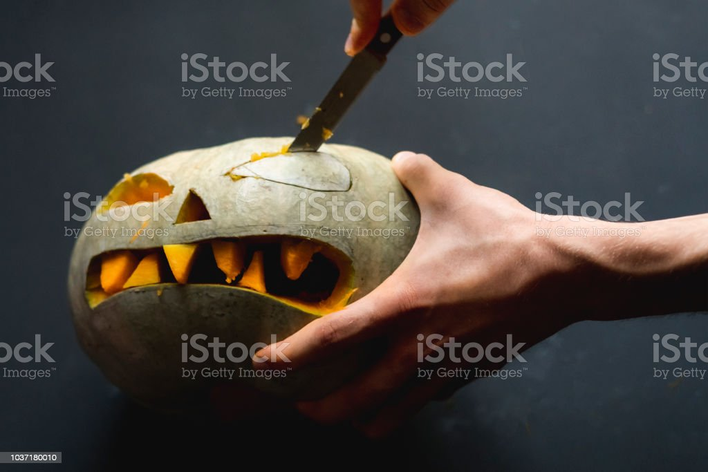 making a pumpkin jack o lantern with carved teeth for halloween concept d – zdjęcie