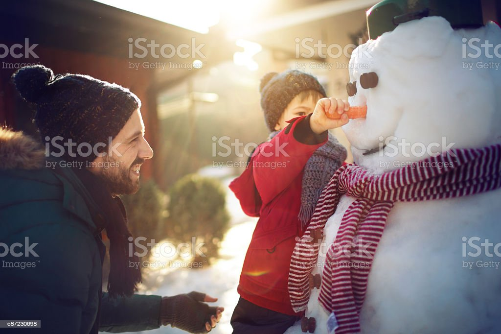 Making a snowman with my dad stock photo