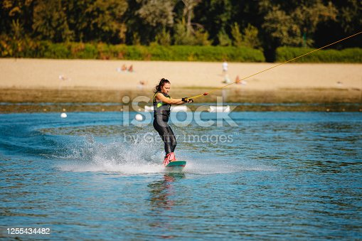 Young woman in wetsuit riding wakeboard on the lake pulled by tow cable, making a soft turn
