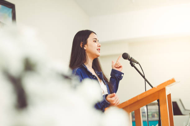 Making a speech Pretty young lady, 18 years old, stands at a podium, maybe in school or at church and she gives a speech or perhaps she is singing. She is confident and accomplished looking. She is on the verge of something. She is mixed of, Asian, Thai and Latina ancestry speech stock pictures, royalty-free photos & images