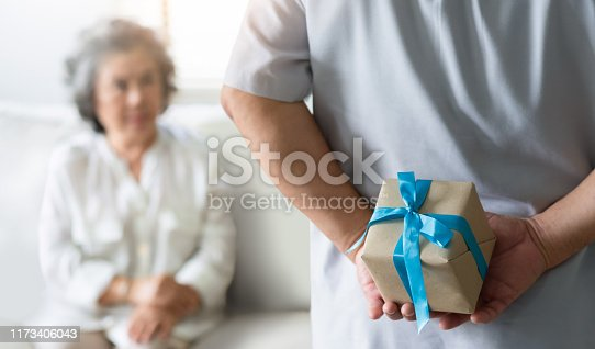 Making a surprise for Christmas and New year concept. Asian Senior man hiding gift box behind his back while his wife sitting and looking to him at their house.