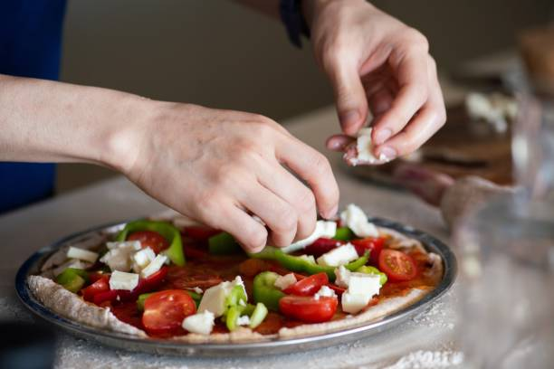 Making a vegetarian pizza at home stock photo