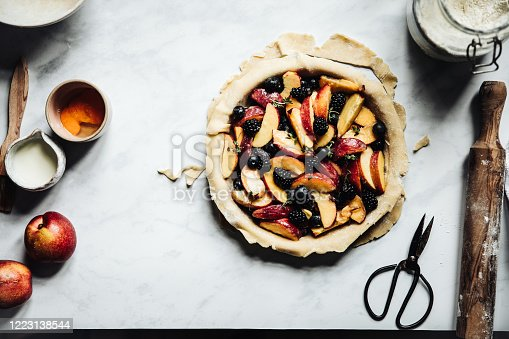 Directly above photograph of a nectarine, blueberry and blackberry lattice fruit pie with a little bit of cognac
