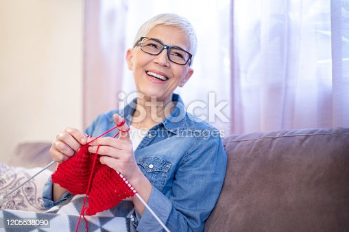 Portrait of beautiful senior woman in casual clothes, wearing eyeglasses knitting warm red scarf for her daughter. She is sitting on sofa covered with a blanket  in her living room.