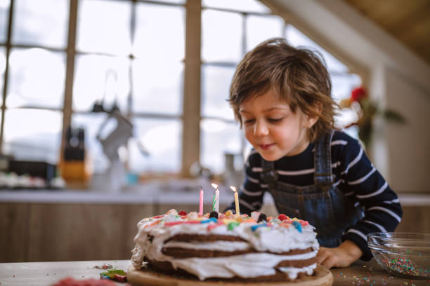 Making a Wish on His Birthday Cute Boy Blowing Birthday Candles at Home birthday candle stock pictures, royalty-free photos & images