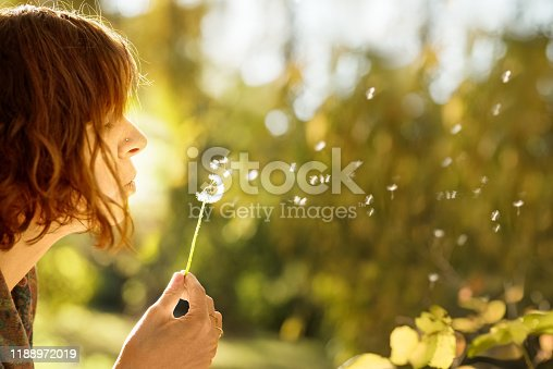 Close-up shot of a young woman blowing dandelion flower in the park on a summer day