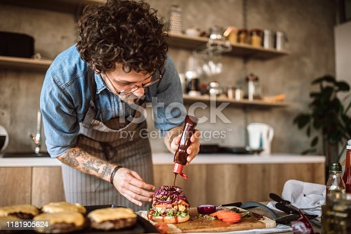Young Male Cook Adding Final Details to Delicious Cheeseburgers