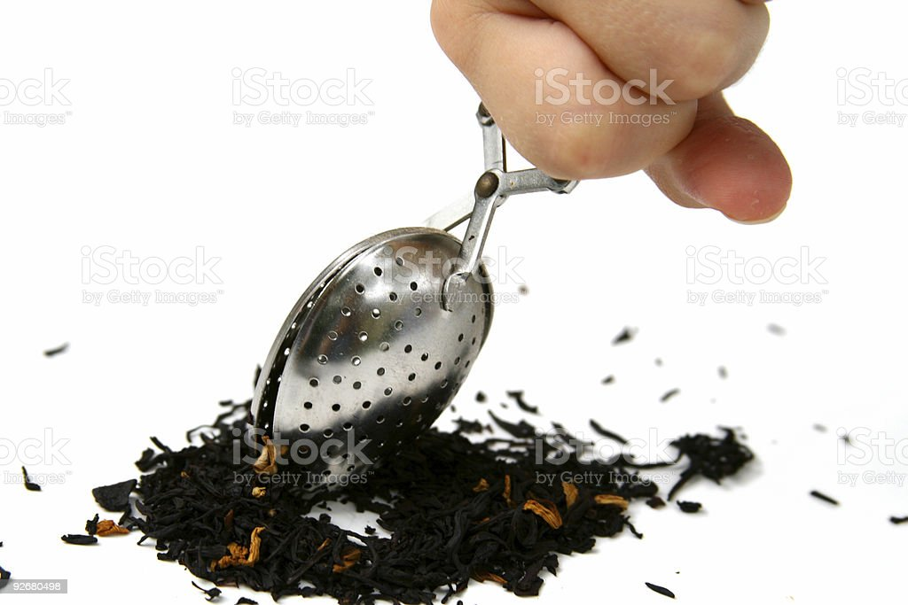 Making Afternoon Tea: Hand holding infuser over loose leaves royalty-free stock photo