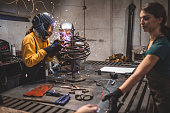 Welder father, working in his workshop with his lovely daughters, making plans and welding stuff.
