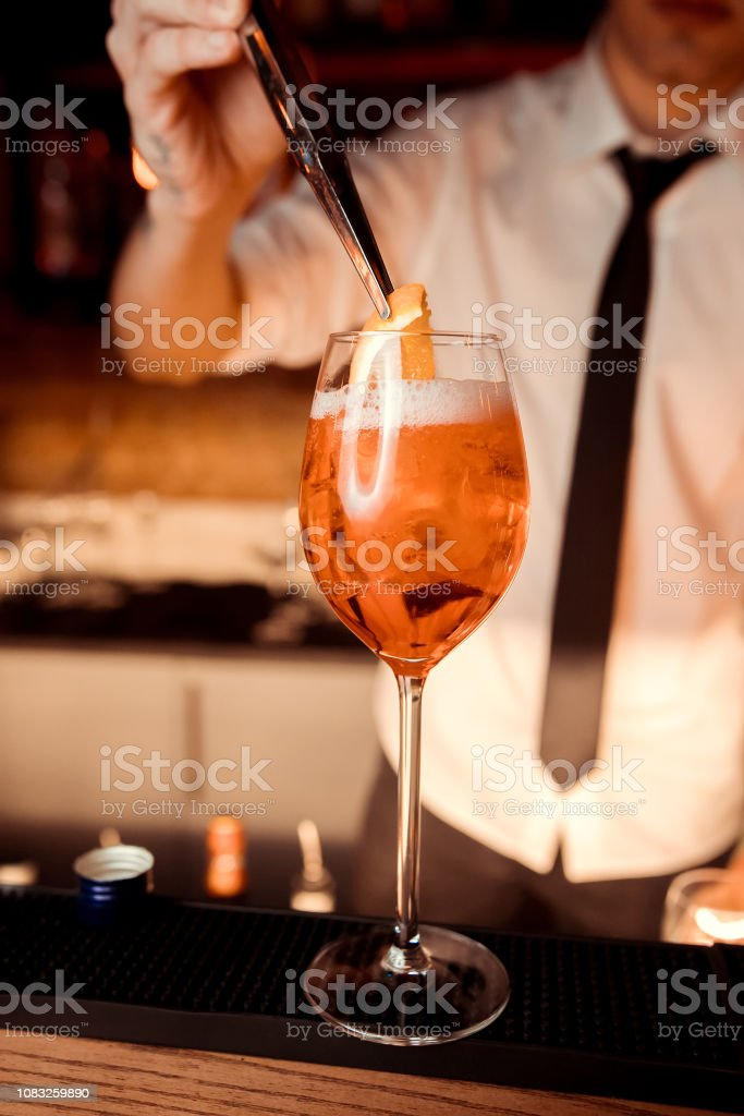 Making Aperol cocktail in wine glass. With ice and orange. stock photo