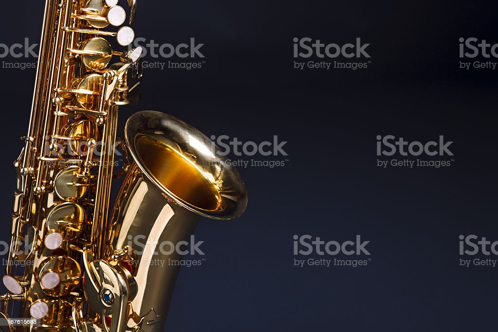 Making beautiful music: golden saxophone against deep blue stock photo
